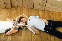 Young couple lying on wooden floor