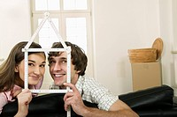 Couple holding ruler in shape of house (thumbnail)