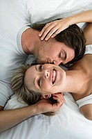 Young couple lying in bed, smiling, kissing, portrait from above