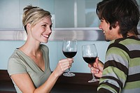 Young couple standing, facing each other, drinking red wine, smiling