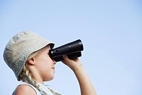 Girl 8_13 standing outdoors using binoculars, close_up