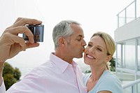 Mature couple on terrace smiling while taking self portrait with camera phone