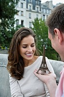 Close up of young couple, man giving present of miniature Eiffel Tower