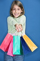 Happy looking young girl holding colourful shopping bags