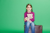 Young girl 8 sitting on suitcase with Teddy, Munich, Bavaria, Germany
