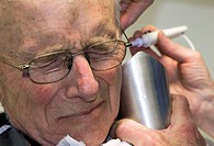 Elderly male patient in a general practice surgery experiences pain during removal of wax from his ear by flushing with warm water. He is holding a co...