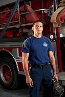 Hispanic fireman standing by fire engine