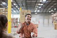 Hispanic man laughing and drinking coffee in warehouse
