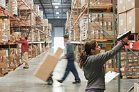 Hispanic woman scanning boxes in warehouse