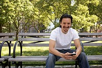 Mixed race man holding cell phone on park bench