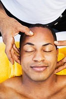 Mixed race man receiving head massage