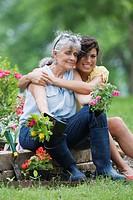 Hispanic granddaughter hugging grandmother in garden