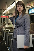 Mixed race businesswoman holding laptop on subway
