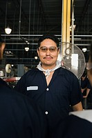 Hispanic man smiling in manufacturing plant