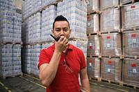 Hispanic man using walkie_talkie in warehouse