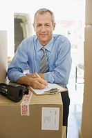 Businessman with clipboard leaning on cardboard box