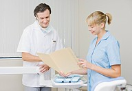 Dentist and dental hygienist reviewing records in dentist's examination room