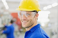 Worker in coveralls and safety goggles smiling