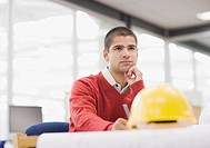 Businessman sitting at table with hard_hat