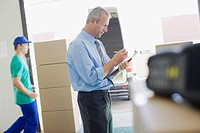 Businessman checking paperwork in warehouse