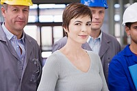 Businesswoman and construction workers standing together
