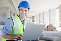 Businessman in hard_hat using laptop on construction site