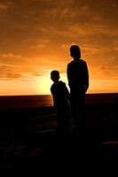 Two boys stand on a beach at sunset with the sun low behind them, turning them into silhouettes