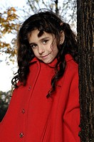 Beautiful five year old girl in red coat standing near a tree in a park