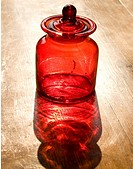 red candy jar reflected on wooden table
