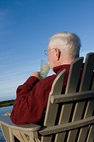 older man drinks lemonade on dock in chair
