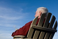 older man gazes into blue sky