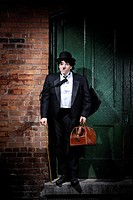 Charlie Chaplin mime Businessman in black suit down-and-out standing at a closed door on the street in a spot of light with stupefied dramatic express...