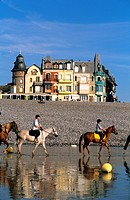 France, Somme, Mers les Bains, horse riders on the beach and in the background villas of the XIXth century