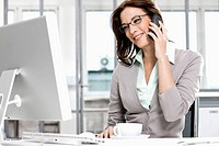 portrait of businesswoman talking on telephone and looking at computer screen