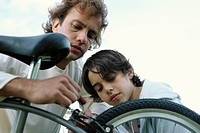 Father and son repairing bicycle together