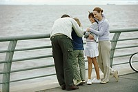 Family together at seaside, parents embracing children, father comforting son