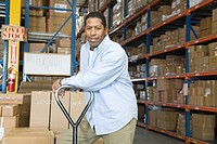 Man leaning on trolley in distribution warehouse portrait