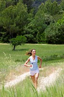 Woman with water bottle running on path through rural field