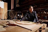 Mature man working in his wood shop.