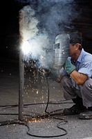 Mature man welding.