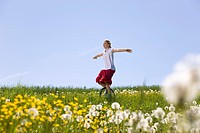 Girl riding unicycle through meadow