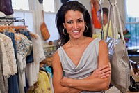 Smiling Hispanic woman with arms crossed in clothing store