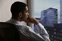 Pensive mixed race businessman looking out office window