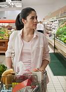 Mixed race woman shopping in supermarket