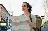 Hispanic woman wearing backpack and holding map in city