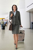 African businesswoman pulling suitcase in airport
