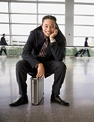 Smiling mixed race businessman sitting on briefcase in airport