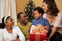 Family holding Christmas gift in living room