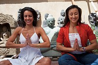 Hispanic women meditating in front of Buddhist statues