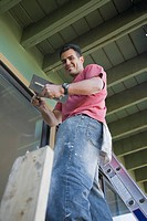 Smiling Hispanic man painting house